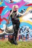 Young woman standing at graffitti wall — Stock Photo