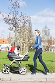 Woman with a pram on spring walk — Stock Photo