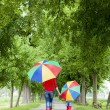 Mother and her daughter with umbrellas in spring alley — Stock Photo #18897357