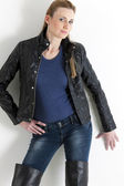 Portrait of standing woman wearing jeans and black jacket — Stockfoto