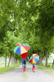 Mother and her daughter with umbrellas in spring alley — Foto Stock