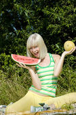 Woman with melons at a picnic — Stock Photo