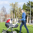 Woman with a pram on spring walk — Stock Photo #19620991