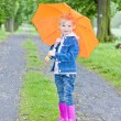 Little girl with umbrella in spring alley — Stock Photo