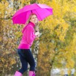Woman wearing rubber boots with umbrella in autumnal nature — Foto Stock