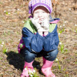 Little girl wearing rubber boots with snowflakes in spring natur - Stock Photo