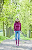 Kvinna som bär gummi stövlar i våren gränd — Stockfoto