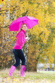Woman wearing rubber boots with umbrella in autumnal nature — Stock Photo