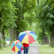 Mother and her daughter with umbrellas in spring alley — Stock Photo #21016897