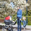 Mother and her daughter with a pram on spring walk — Stock Photo