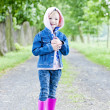 Little girl wearing rubber boots in spring alley — Stock Photo #21566047