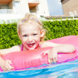 Stock Photo: Little girl with rubber ring in swimming pool