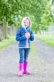 Little girl wearing rubber boots in spring alley — Stock Photo