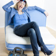 Woman wearing blue clothes with handbag sitting on sofa - Stock Photo