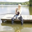 Fishing woman sitting on pier - Stock Photo