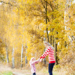 Mother with her daughter in autumnal alley — Stock Photo #22518747