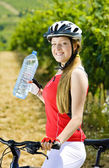Biker with bottle of water in vineyard — Stock Photo