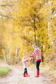 Mother with her daughter in autumnal alley — Foto Stock