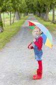Little girl with umbrella in alley — Stock Photo