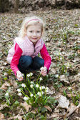 Little girl with snowflakes in spring nature — Stock Photo