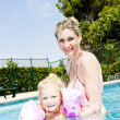 Mother with her daughter in swimming pool — Stock Photo #23607425