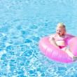 Little girl with rubber ring in swimming pool — Stock Photo #23607897
