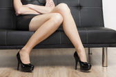 Detail of woman wearing black pumps sitting on sofa — Stock Photo
