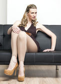 Woman wearing brown pumps sitting on sofa — Stockfoto