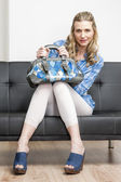Woman wearing denim clogs with a handbag sitting on sofa — Foto de Stock