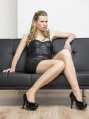 Woman wearing black dress and pumps sitting on sofa — Foto de Stock