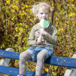 Little girl with a lollipop sitting on bench in spring — Stock Photo #25050285