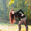 Young woman in autumnal nature - Stock Photo