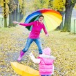 Mother and her daughter with umbrellas in autumnal alley — Stock Photo #25051233