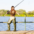 Young woman fishing at pond — Stockfoto