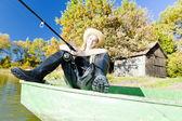 Fishing woman sitting on boat — Stock fotografie