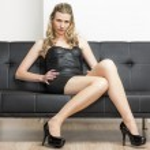 Woman wearing black dress and pumps sitting on sofa — Stock Photo
