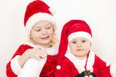 Zwei kleine mädchen als weihnachtsmänner — Stockfoto