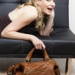 Portrait of woman with a handbag lying on sofa — Photo