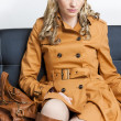 Woman wearing brown coat sitting on sofa — Stock Photo