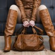 Detail of sitting woman in brown clothes holding a handbag — Stock Photo