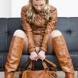 Woman wearing brown jacket and boots sitting on sofa — Stock Photo