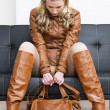 Woman wearing brown jacket and boots sitting on sofa — Stock Photo #27362823