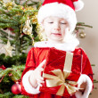 Little girl as Santa Claus with Christmas present — Stockfoto #27364491
