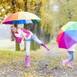 Mother and her daughter with umbrellas in autumnal alley — Stock Photo #27364805
