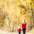 Mother with her daughter in autumnal alley — Stock Photo #27364865