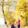 Woman with a pram on walk in autumnal alley — Stock Photo