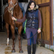 Stock Photo: Equestriwith her horse in stable
