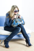 Woman wearing blue clothes with handbag sitting on sofa — Stock Photo