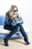 Donna che indossa vestiti blu con borsetta seduto sul divano — Foto Stock