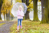 Little girl with umbrella in autumnal alley — Stock Photo